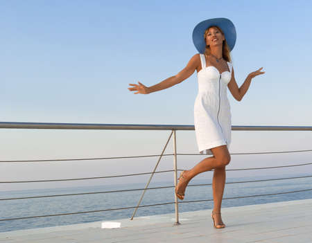 Elegant sexy woman in white dress dancing near railings at sunset  Like yacht style  Stock Photo