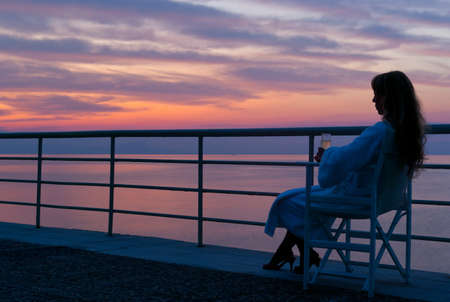 Woman sitting on a beach and watching the mythical colorful sunset