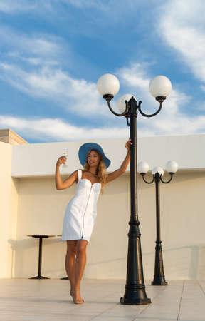 Luxury woman in white dress posing near street lamp at sunset