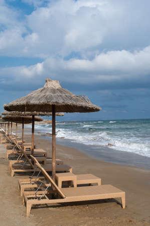 Empty beach chairs under umbrellas on Mediterranean beach in the morning