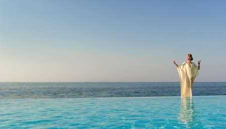 Woman in long dress like greek goddess posing near edge of infinity pool on a beach Stock Photo