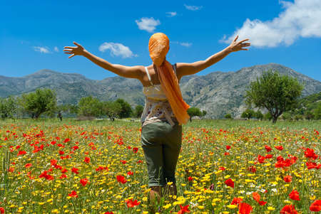 Happy young woman standing in flower colorful field on Lasithi Plateau. Greece. Crete