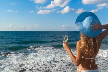 性感的女人在比基尼和帽子与一杯葡萄酒看着大海。克里特岛。希腊