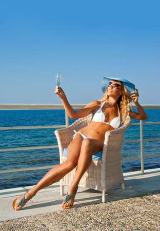 Sexy woman white bikini relax in armchair on Mediterranean coast. Crete. Greece