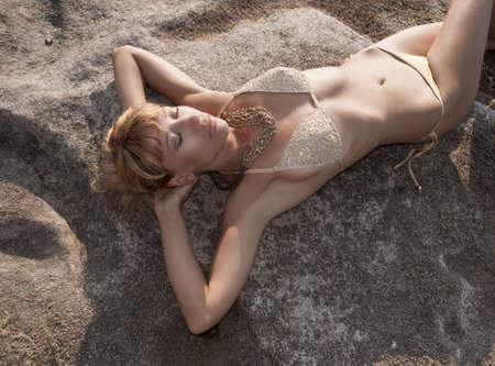Portrait of sexy woman in gold bikini sunbathing on beach stones. Greece.