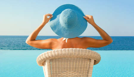 Attractive woman in hat relax near edge of infinity pool and looking to horizon in sunny day Stock Photo