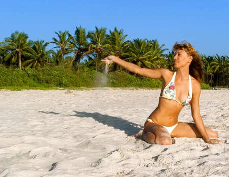 Happy woman in bikini enjoy on a tropical Goa beach