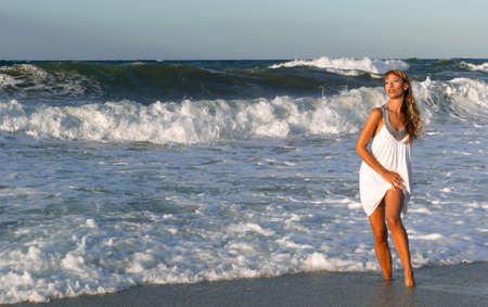 Sexy woman in white dress posing on the sea coast at sunset
