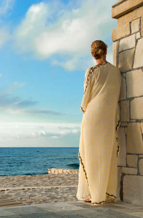 Greek style woman in long silk dress looking for the sea photo