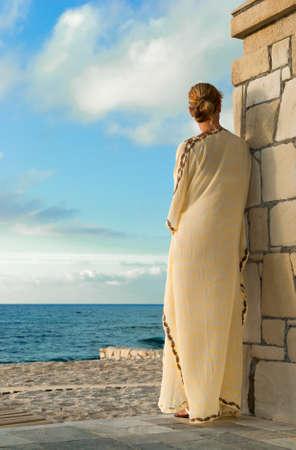 Greek style woman in long silk dress looking for the sea
