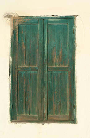 Vintage closed window with wooden shutters in an wall