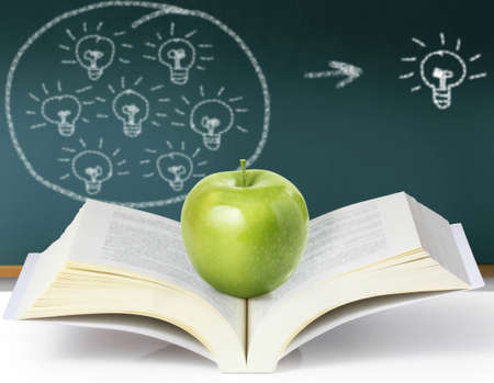 green apple on a book and the blackboard