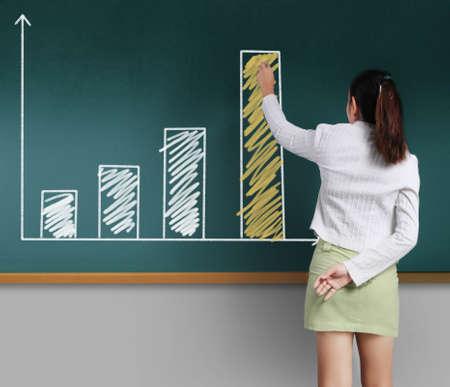 ビジネスの女性を黒板にグラフを表示 写真素材