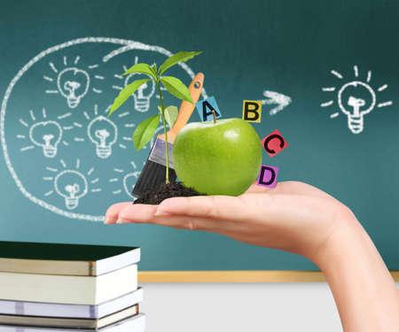 educators: mano con manzana verde y las ideas educativas