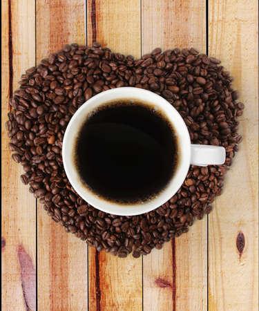 tomando refresco: Taza de caf� caliente en forma de coraz�n hecha de caf� sobre fondo de madera Foto de archivo