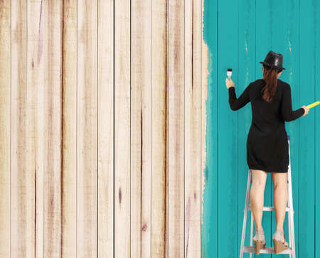 young woman painting house photo