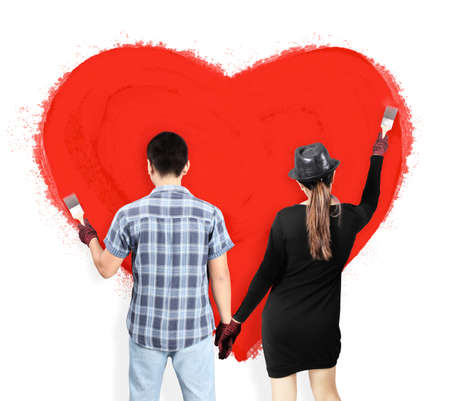 Young caucausian couple paint brushes Heart  together photo