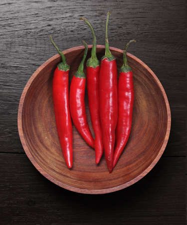 Red Hot Chili Peppers in bowl over wooden  photo