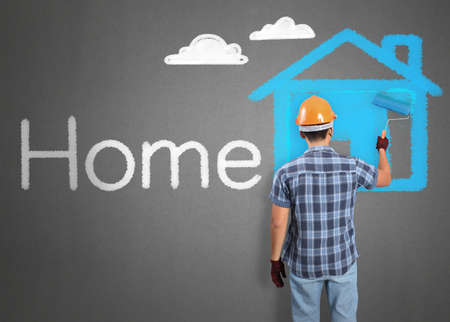 house painter: man decorating or painting house with a paint brush