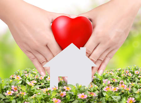 care at home: Heart in a hands  floral background and home