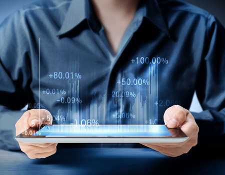 holding touch screen tablet with a graph  Stock Photo
