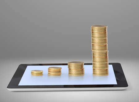 Tablet with a graph,gold coins photo