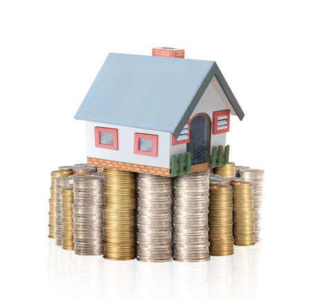 repossession: house placed on a pile of gold coins isolated on white background