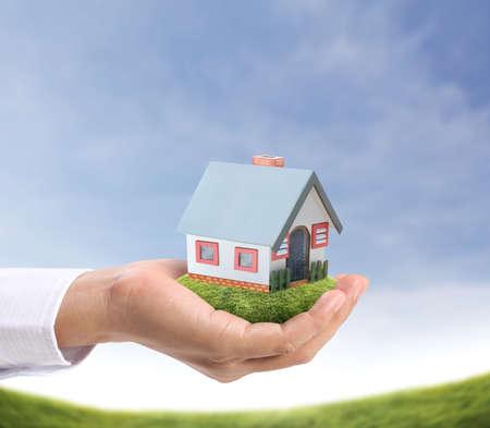 жилье: проведения дом, представляющий домовладения и бизнеса в сфере недвижимости Фото со стока