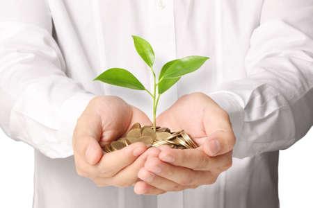 wartości: Biznesmen gospodarstwa roślin wyrastające z garścią monet Zdjęcie Seryjne