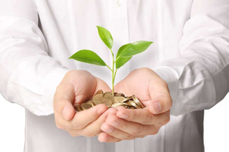 pile of money: Businessman holding plant sprouting from a handful of coins  Stock Photo