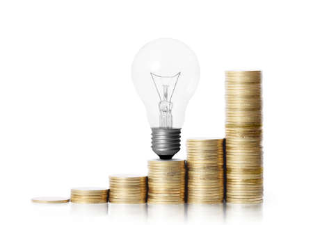 money market: light bulb on gold coins and graph them isolated on white background  Stock Photo