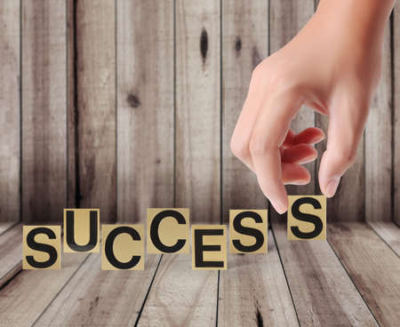Hand and word success on a wood background  photo