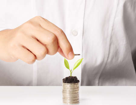 ron: Businessman holding plant sprouting from a handful of coins