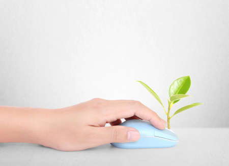 carbon emission: hands using a mouse with a plant
