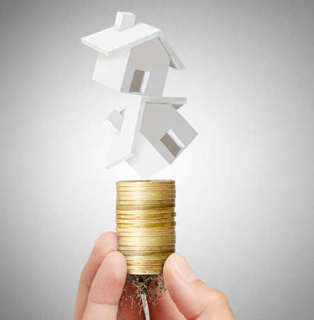 Mortgage concept by money house from coins in hand photo