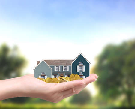 protect home: holding house representing home ownership and the Real Estate business holding house and coins  Stock Photo