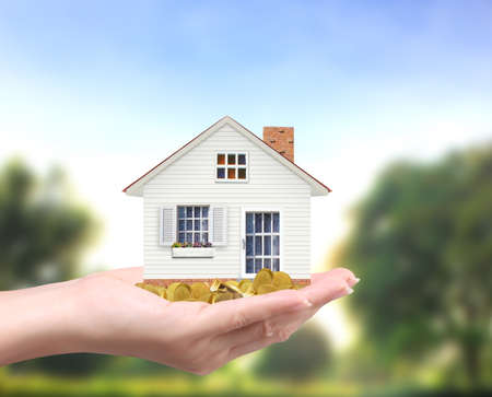 holding house representing home ownership and the Real Estate business holding house and coins Stock Photo