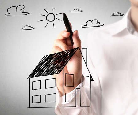mortgage rates: Man drawing a growing real estate chart