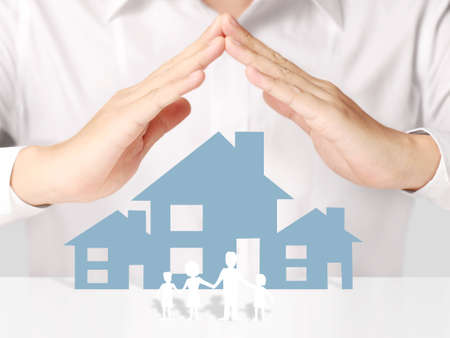 assure: holding house representing home ownership and the Real Estate business Stock Photo