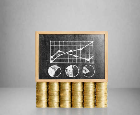 storage compartment: Blackboard with business on golden coin Stock Photo