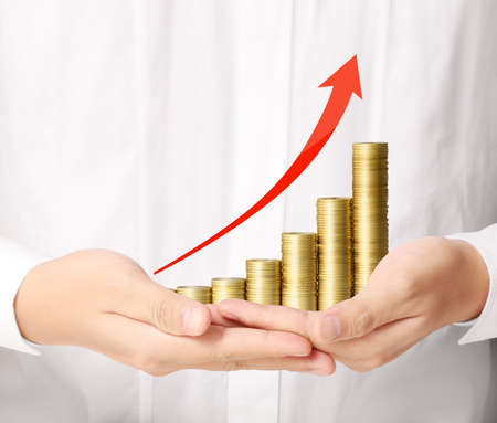 Coins and graph in hand, investment concept Stock Photo