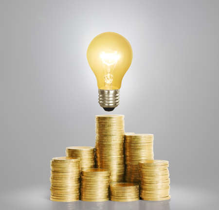 financial concept: Bulb With Stack Of a Coins Stock Photo