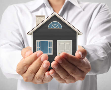 assure: holding house representing home ownership and the Real Estate busines Stock Photo