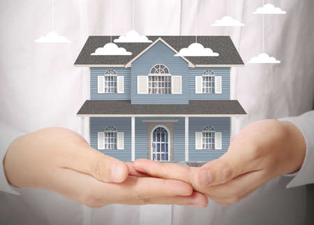 is real: holding house representing home ownership and the Real Estate business Stock Photo