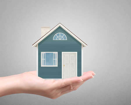 home ownership: holding house representing home ownership and the Real Estate busines Stock Photo
