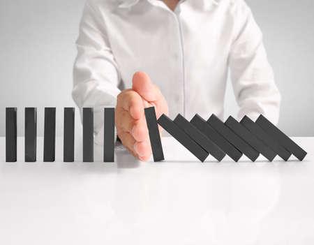 main arrêter un domino continue renversé Banque d'images