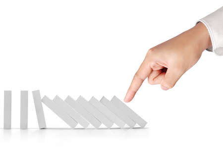 intervene: Hand pushing a dominoes concept Stock Photo