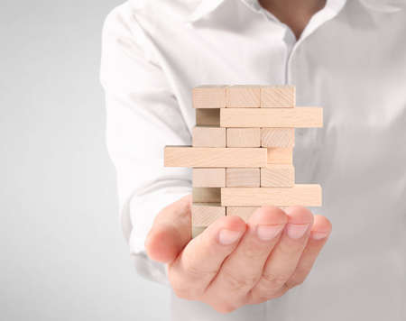 making a pyramid with empty wooden cubes Stock Photo