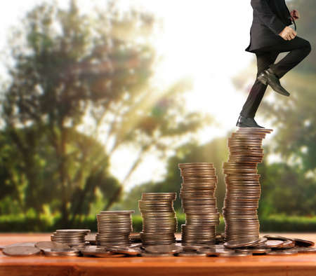Businessman walk on stack of coins which grows success and investment