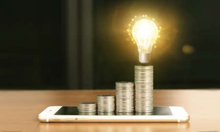 light bulb on top of coins and a smartphone